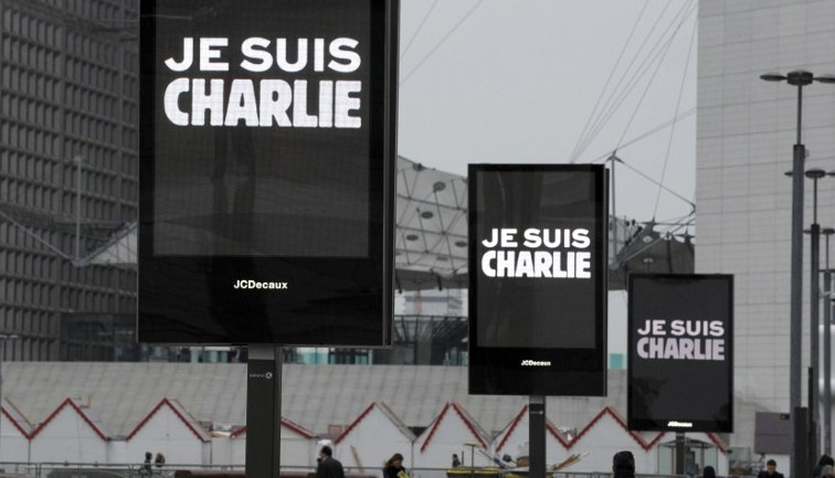 """Signs read """"Je suis Charlie"""" (I am Charlie) near La Defense in Paris before the nation observed a minute of silence on January 8, 2015 for the 12 victims of an attack by armed gunmen on the offices of French satirical newspaper Charlie Hebdo in Paris the day before. (photo credit: AFP/ERIC PIERMONT)"""