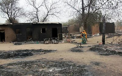 A woman walking past burnt houses after a two-day clash between officers of the Joint Task Force and members of the Islamist sect Boko Haram, in Baga, Borno, April 21, 2013. (photo credit: AFP PHOTO/STRINGER)