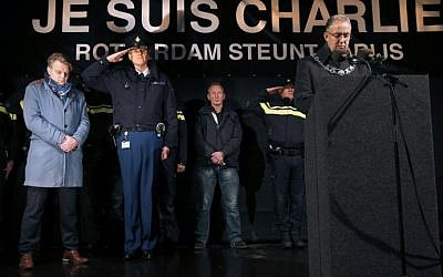 Mayor of Rotterdam, Ahmed Aboutaleb (R), chief-editor of Dutch newspaper Algemeen Dagblad Christiaan Ruesink (L) and Frank Pauw (C) deputy chief constable of the police in Rotterdam observe a minute of silence in front of a banner reading 'I am Charlie' at Square 1940, in Rotterdam on January 8, 2015. (photo credit: Jerry Lampen/AFP)