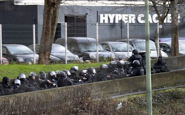 A photo taken on January 9, 2015 shows members of the French police forces taking position by the kosher grocery store in Saint-Mande, near Porte de Vincennes, eastern Paris, where a gunman opened fire at the kosher grocery store and took at least five people hostage, sources told AFP. (Photo credit: AFP / ERIC FEFERBERG)