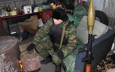 A Pro-Russian separatist warms himself beside a stove at a checkpoint in the eastern Ukrainian city of Donetsk during -15C conditions on January 9, 2015. (photo credit: AFP/ ALEXANDER GAYUK)