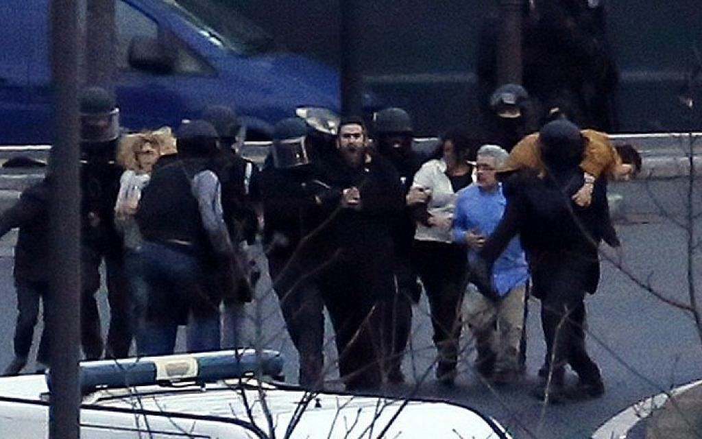 Members of the French police special forces evacuate the hostages after launching the assault at a kosher grocery store in Porte de Vincennes, eastern Paris, on January 9, 2015. (Photo credit: AFP/ THOMAS SAMSON)