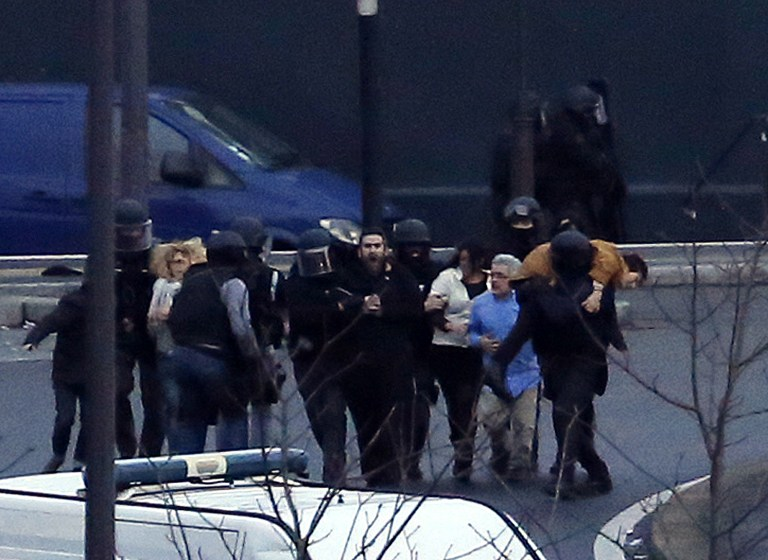 A security officer directs released hostages after they stormed a kosher market to end a hostage situation, Paris, Friday, Jan. 9, 2015.  (Photo credit: AP/Michel Euler)