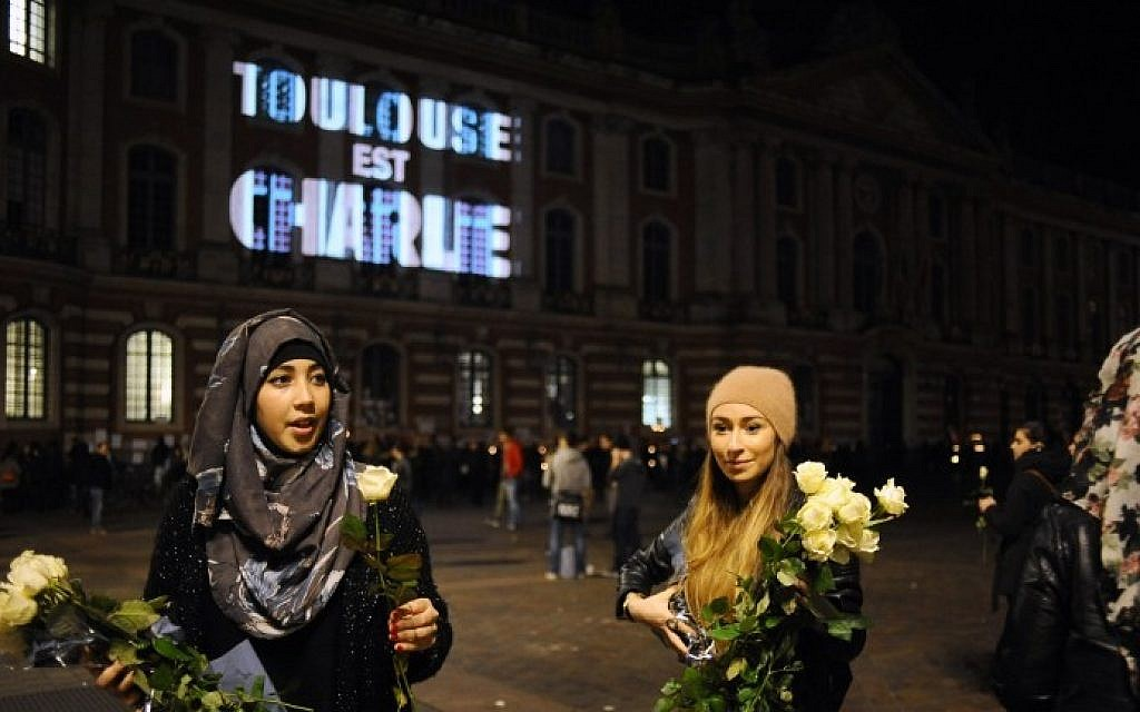 "Women give out white roses near the Capitole building in Toulouse, southern France, where on the facade is projected the words ""Toulouse est Charlie"" (Toulouse is Charlie), on January 9, 2015 (Photo credit: Remy Gabalda/AFP)"