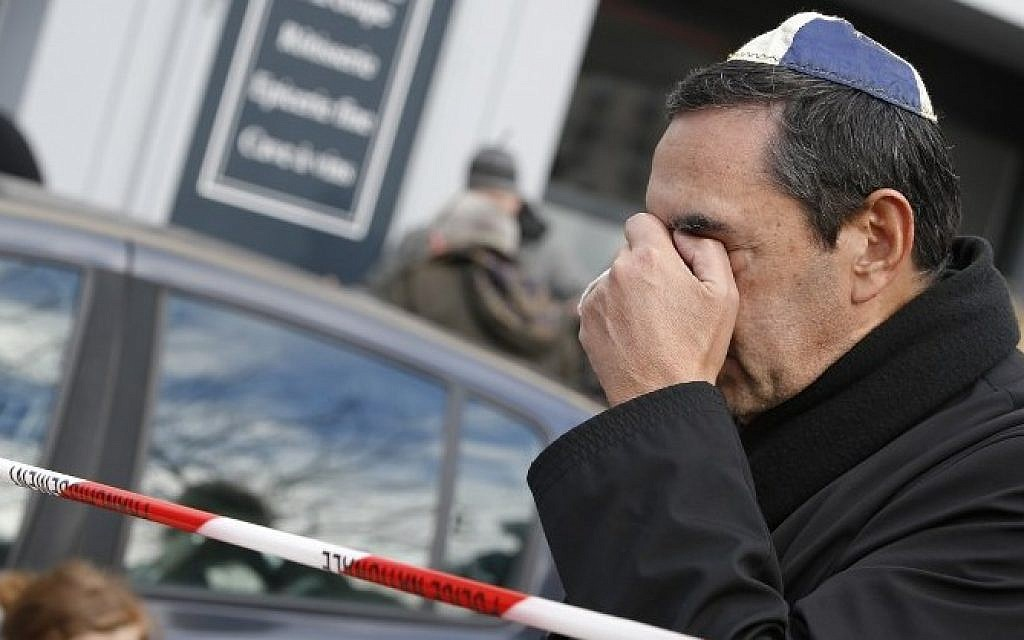 A man wearing a kippa cries near a kosher grocery store in Porte de Vincennes, in eastern Paris, on January 10, 2015, a day after four people were killed at the Jewish supermarket by jihadist gunman Amedy Coulibaly during a hostage-taking. (Photo credit: AFP/ KENZO TRIBOUILLARD)