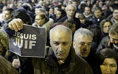 "File: A man holds a sign reading ""I am Jewish"" during a demonstration in Paris on January 10, 2015. (Kenzo Tribouillard/AFP)"