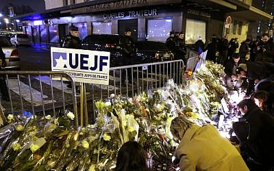 People place candles on January 10, 2015 during a demonstration at the end of Shabbat called by the Jewish Student's Union of France at the Porte de Vincennes in eastern Paris in homage to the four victims of the January 9, 2015 attack at a kosher supermarket in the French capital. (photo credit: AFP/KENZO TRIBOUILLARD)