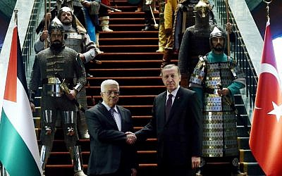 Turkish President Recep Tayyip Erdogan, right, and Palestinian President Mahmoud Abbas shake hands in front of 16 soldiers who represent the 16 Turkish states founded in the past at the presidential palace in Ankara, Turkey on January 12, 2015. (photo credit: AFP/ADEM ALTAN)