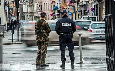 Illustrative photo of a French police officer and a soldier on patrol, January 13, 2015. (AFP/Philippe Huguen)