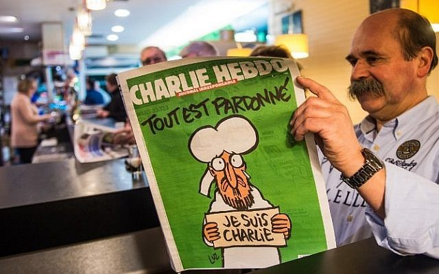 A man reads the latest edition of French satirical weekly Charlie Hebdo at a cafe in Dunkirk on January 14, 2015 shortly after the edition went on sale (photo credit: AFP/PHILIPPE HUGUEN)