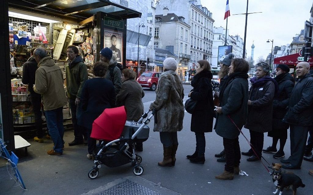 People wait outside a kiosk in Paris on January 14, 2015 as the latest edition of French satirical magazine Charlie Hebdo went on sale. (photo credit:  AFP PHOTO / BERTRAND GUAY)