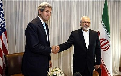 Iranian Foreign Minister Mohammad Javad Zarif (right) shakes hands with then US secretary of state John Kerry (left) in Geneva, January 14, 2015. (AFP/Rick Wilking/Pool)