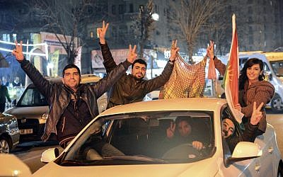 Kurds celebrate as they drive along a street in Diyarbakir, southeastern Turkey, on January 26, 2015, following news that Kurdish fighters expelled Islamic State fighter from the Syrian border town of Kobani. (photo credit: AFP/ILYAS AKENGIN)