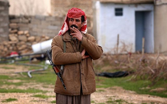 An armed Yazidi man smokes a cigarette on January 15, 2015 in the village of Sinuni, in the northwestern Sinjar area, which Iraqi Kurdish forces recaptured from Islamic State group fighters. (AFP/Safin Hamed)