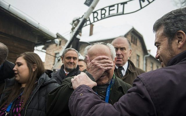Holocaust survivor Mordechai Ronen, from the US, is comforted by his son as he is overcome by emotion standing next to President of the World Jewish Congress Ronald Lauder, second right, as he arrives at the former Auschwitz concentration camp on January 26, 2015. photo credit: AFP/ODD ANDERSEN)