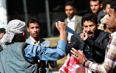 A Shiite Houthi rebel threatens Yemeni protesters during a rally against the control of the capital by Houthi rebels on January 24, 2015 in the capital Sanaa. (Photo credit: AFP / MOHAMMED HUWAIS)