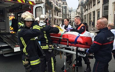 Firefighters carry an injured man on a stretcher in front of the offices of the French satirical newspaper Charlie Hebdo in Paris on January 7, 2015 (photo credit: AFP PHOTO / PHILIPPE DUPEYRAT)