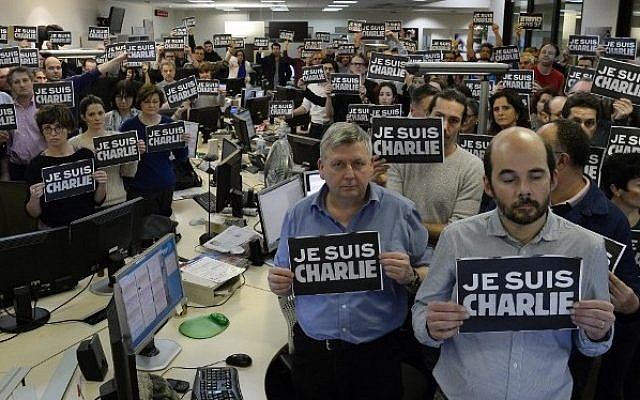 "Journalists hold placard reading ""I am Charlie"" as they hold a minute of silence, on January 7, 2015 at the offices of French news agency Agence France Presse, following the attack by gunmen in the offices of the French satirical weekly Charlie Hebdo. (Photo credit: AFP/BERTRAND GUAY)"