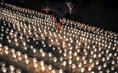 A woman lights a candle during a gathering in Lyon, central eastern France, on January 7, 2015, following an attack by unknown gunmen on the offices of the satirical weekly, Charlie Hebdo. (photo credit: AFP/ JEFF PACHOUD)