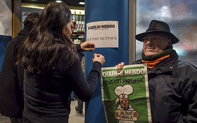 "A sign which translates as ""Charlie Hebdo - Sold Out"" is displayed as a customer holds a copy of the magazine outside a newsagents in Dunkirk on January 14, 2015. (photo credit: AFP/PHILIPPE HUGUEN)"
