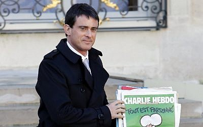 French Prime Minister Manuel Valls, holding the latest edition of French satirical magazine Charlie Hebdo, leaves the Elysee Palace after a weekly cabinet meeting on January 14, 2015 in Paris (photo credit: AFP/PATRICK KOVARIK)