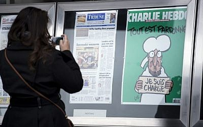 A woman takes a photo of the cover of the French satirical newspaper Charlie Hebdo featuring the Prophet Mohammed displayed with front pages for newspapers from around the world outside the Newseum January 14, 2015 in Washington, DC. (Photo credit: AFP PHOTO/BRENDAN SMIALOWSKI)