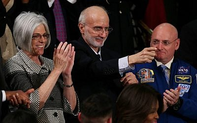 Alan Gross, recently freed after being held in Cuba since 2009, points back at US President Barack Obama after being recognized during the State of the Union speech in the House chamber of the US Capitol January 20, 2015 in Washington, DC.  (Photo credit: Alex Wong/Getty Images/AFP)