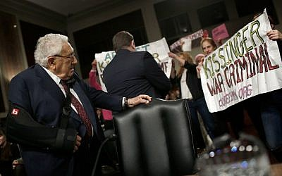 Protesters shout 'Arrest Kissinger for war crimes' as former US secretary of state Henry Kissinger (left) arrives for testimony before the Senate Armed Services Committee, in Washington, DC,  January 29, 2015. (photo credit: AFP/Win McNamee/Getty Images)
