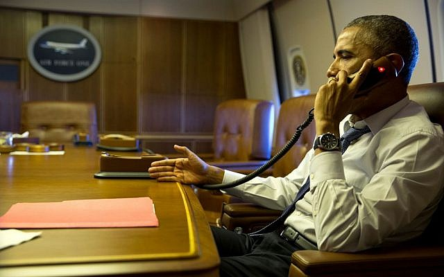 Barack Obama speaking on the phone from aboard Air Force One on January 7, 2015. (photo credit: Pete Souza/White House)