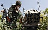 In this May 22, 2010 photo, a Hezbollah fighter stands behind an empty rocket launcher while explaining  various tactics and weapons used against Israeli soldiers on the battlefield. (AP/Hussein Malla)