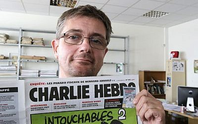 "In this Sept.19, 2012 file photo, Stephane Charbonnier also known as Charb , the publishing director of the satyric weekly Charlie Hebdo, displays the front page of the newspaper as he poses for photographers in Paris. Masked gunmen shouting ""Allahu akbar!"" stormed the Paris offices of the newspaper on Jan.7, 2015, killing 12 people including Charb, before escaping. It was France's deadliest terror attack in at least two decades. (photo credit: AP Photo/Michel Euler, File)"