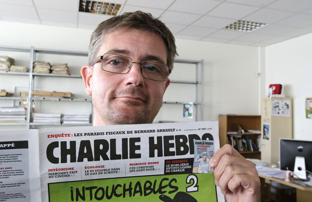 "In this Sept.19, 2012 file photo, Stephane Charbonnier also known as Charb, the publishing director of the satyric weekly Charlie Hebdo, displays the front page of the newspaper as he poses for photographers in Paris. Masked gunmen shouting ""Allahu akbar!"" stormed the Paris offices of the newspaper on Jan. 7, 2015, killing 12 people including Charb, before escaping. It was France's deadliest terror attack in at least two decades. (photo credit: AP Photo/Michel Euler, File)"
