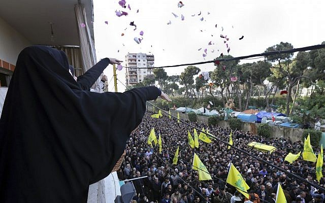 Lebanese women throw flowers on January 19, 2015 as Hezbollah supporters carry the coffin of Jihad Mughniyeh, the son of Imad Mughniyeh, who was killed in the air strike on the Syrian side of the Golan Heights (photo credit: AP/Bilal Hussein)