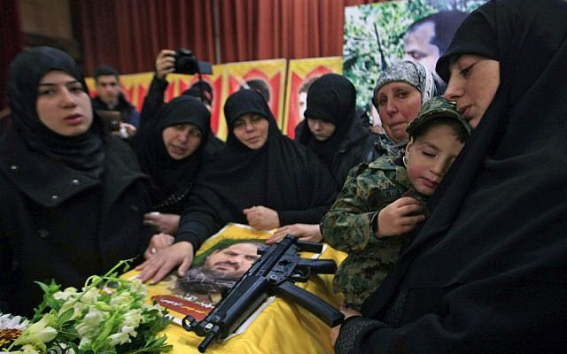 The sister of Hezbollah member Mohammad Issa who was killed in an Israeli airstrike in Syria on Sunday, holds his son Ahmed as she mourns over his coffin during his funeral procession, in the southern village of Arab Salim, Lebanon, Tuesday, Jan. 20, 2015 (photo credit: AP/Mohammed Zaatari)