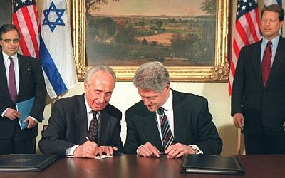 President Bill Clinton looks on Israeli prime minister Shimon Peres writes the president's name in Hebrew after they sign a joint declaration on terrorism, Tuesday April 30, 1996 at the White House. (photo credit: AP Photo/Ruth Fremson)