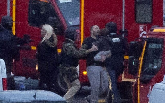 A security officer directs released hostages after French security forces stormed a kosher market to end a hostage situation, Paris, Friday, Jan. 9, 2015.  (Photo credit: AP/Michel Euler)