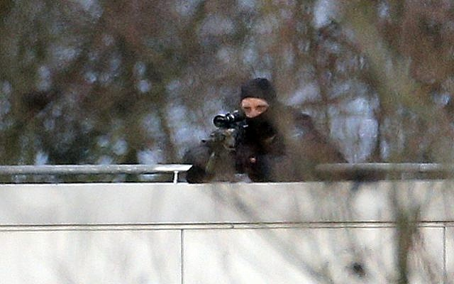 A hooded police officer takes aim from a rooftop in Dammartin-en-Goele, northeast of Paris, where the two brothers suspected in a deadly terror attack on a French magazine were cornered, Friday, January 9, 2015. (photo credit: AP Photo/Christophe Ena)