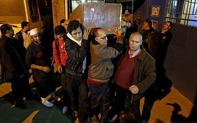 The coffin of Shaimaa el-Sabagh is carried out of the Zenhom morgue in Cairo, Egypt early Sunday, Jan. 25, 2015 (AP Photo/Ahmed Abd El-Gwad, El Shorouk Newspaper)