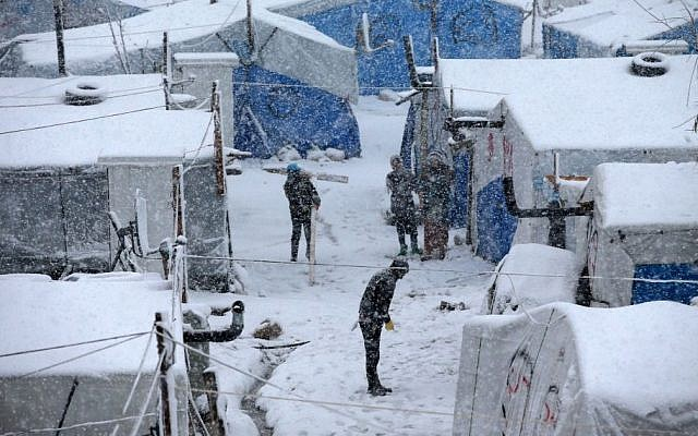Syrians stand between their tents as they prepare to remove the snow from the top of their tents at a refugee camp in Deir Zannoun village, in the Bekaa valley, east Lebanon, Wednesday, Jan. 7, 2015. (Photo credit: AP/Hussein Malla)
