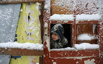 A Syrian boy looks out through his tent door covered in snow at a refugee camp in Deir Zannoun village, in the Bekaa valley, east Lebanon, Wednesday, Jan. 7, 2015. (AP Photo/Hussein Malla)