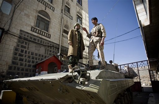 Houthi Shiite Yemeni wearing army uniforms stand atop an armored vehicle, which was seized from the army during recent clashes, outside the house of Yemen's President Abed Rabbo Mansour Hadi in Sanaa, Yemen, Thursday, Jan. 22, 2015. (photo credit: AP Photo/Hani Mohammed)