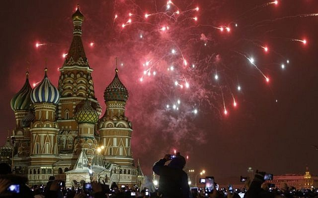 People photograph fireworks as they celebrate the New Year in Red Square in Moscow, Russia, Thursday, Jan. 1, 2015. (Photo credit: AP/Denis Tyrin)
