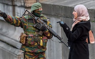 A Belgian security officer talks with a woman as he patrols near the Palace of Justice, where suspects wanted in Belgium on terrorism-related charges were set to appear before the federal court, in Brussels,, January 21, 2015. (photo credit: AP/Geert Vanden Wijngaert)