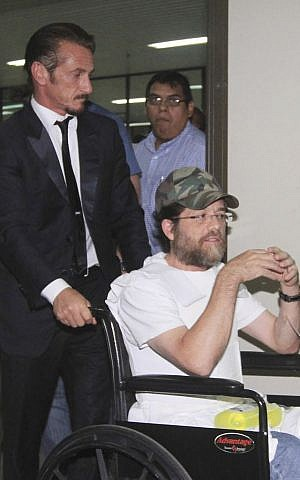In this Dec. 11, 2012 file photo, actor Sean Penn pushes US businessman Jacob Ostreicher in a wheelchair, during a recess at Ostreicher's hearing in Santa Cruz, Bolivia.(photo credit: AP Photo, File)