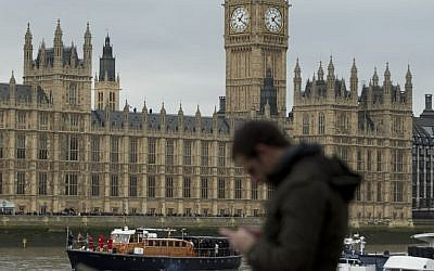 A man looks at his smartphone in front the Palace of Westminster in London, Friday, Jan. 30, 2015. (photo credit: AP Photo/Alastair Grant, illustrative)