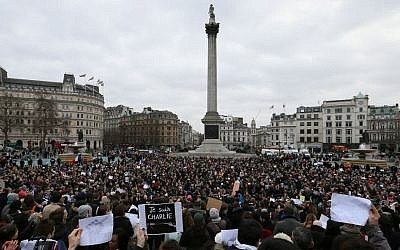 People stand for a memorial gathering for the victims of the recent terrorist attacks in France, held in Trafalgar Square, London, Sunday, Jan. 11, 2015. (photo credit: AP/Tim Ireland)