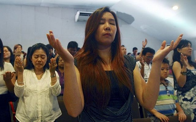 Members of Mawar Sharon church attend a prayer service for the relatives of lost loved ones aboard the AirAsia Flight 8501, in Surabaya, East Java, Indonesia Sunday, Jan. 4, 2015. About 40 members of the church were aboard the plane which crashed into the Java Sea a week ago. (Photo credit: AP/Firdia Lisnawati)