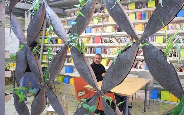 A man sits in the free lending library at the Central Bus Station, which has books in 12 languages and operates on an honor system. (photo credit: Melanie Lidman/Times of Israel)