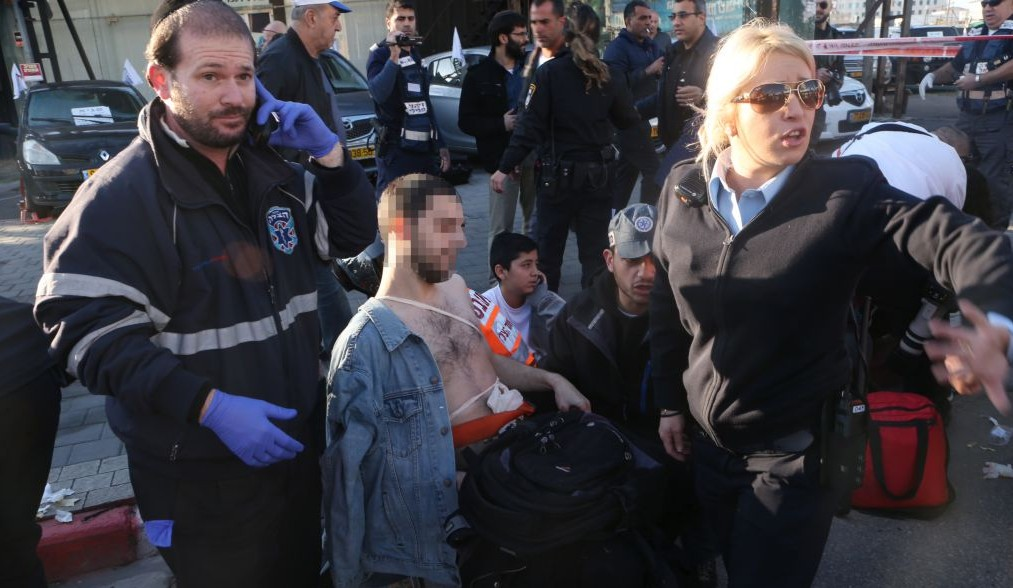 Medics and police evacuate an Israeli man who was injured in a stabbing attack on the No. 40 Dan bus in Tel Aviv on January 21, 2015. (photo credit: Flash90)