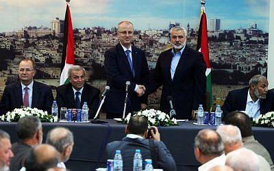 Palestinian Prime Minister Rami Hamdallah shakes hands with senior Hamas leader Ismail Haniyeh, at Haniyeh's house in Gaza city on October 9, 2014